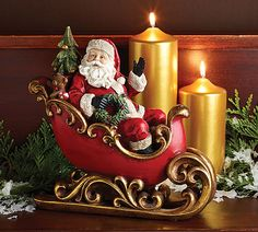 """#burtonandburton Hand-painted resin red sleigh trimmed in gold with gold blades. Santa sitting inside waving. Toys and Christmas Tree around him.<br><br>9 1/4""""H X 10""""W X 4""""D.<br>1 set of 2."""