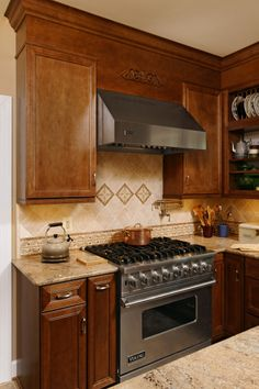 Kitchen Remodel, Daniels Design and Remodeling, dark cabinets, glass cabinets, island, countertops, open space, luxurious, tile floors, contemporary, granite countertops, hanging lights, light colored walls, back splash pattern