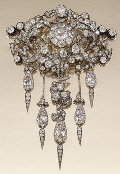 DIAMOND DEVANT DE CORSAGE, 1860S.  Of foliate design, centring on a diamond cluster within an open work surround of acanthus and ivy leaves, suspending five articulated pendant drops, set with cushion-, pear-shaped, circular- and rose-cut diamonds, further embellished with cushion-shaped and circular-cut stones in cut-down collets, later brooch fitting, original fitted case.