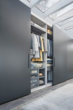 LEMA | ELLEVI by Officinadesign Lema is characterised by a minimal look that stands out for the handle embedded in the door with tone-on-tone background or in contrast with the door finish. The interior equipment offers combinations that can be tailored to the needs of each individual order. Here, the pull-out trouser rack next to open shelving of various dimensions.