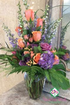 Enjoy the soft colors of lavender and peach in this exquisite bouquet. Lavender hydrangeas, kale, delphinium, roses are accented by peach roses, spray roses and hypericum. Lacey foliages soften the design.