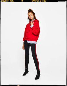 Look en negro, rojo, azul y blanco de Bershka - Look sporty en rojo. Conjunta unos pantalones ajustados negros con franja lateral en rojo, camisa en tonos azules y sudadera en rojo. Este look te muestra que el rojo se puede combinar con varios colores.