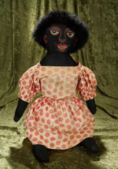 """25"""" Exceptional American Black Sateen Folk Doll~~~Black cotton sateen cloth doll with flat-dimensional face, painted button pupils, oil-painted features with pronounced eyelashes and double row of teeth, smiling expression, black curly wig, antique cotton romper and panties. American, circa 1900, exceptional imaginative folk painting of features."""