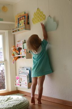 DIY front-facing book shelves made of spice racks.  I love that they're kid-level and the paper clouds are cute, too :)