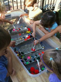 Sensory table: cardboard egg cartons, pom poms, and plastic spoons