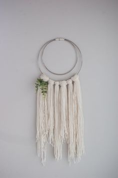 This is one of our medium wall hangings, perfect for any space, with plant accent and silver rings. + off white cream color + layered silver metal rings + small plant accent + 100% yarn + handmade * due to the custom nature of our items they may vary slightly