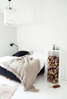 A white bedroom with a stack of logs in the nightstand... there's no doubt you'd stay warm in this space