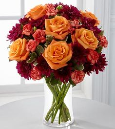 Birthday Flowers - FTD Autumn Treasures Bouquet - The FTD Autumn Treasures Bouquet is a floral fantasy of fall color displayed in eye-catching jewel tones. Brilliant orange roses and orange mini carnations are accented with burgundy chrysanthemums and lush greens arranged to perfection in a classic clear glass vase to create a warm and dazzling way to send your best wishes for a beautiful harvest season.BEST bouquet includes 22 stems. Approximately 15H x 13W.