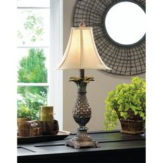 A classic symbol of hospitality, this lovely pineapple lamp will be a welcome addition to your decor! The detailed base features timeless styling and is topped with a neutral shade to complement right into your living space.