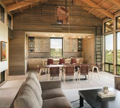 Modern cabin with weathered interior finishes and sleeping loft above the kitchen - Lake Flato