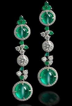 A pair of cat's eye emerald and diamond pendent earrings Each formed as a series of three 'target' design plaques, two of which are set with a round cabochon cat's eye emerald surrounded by a row of brilliant-cut diamonds, the central plaque set with a brilliant-cut diamond with similar surround, all joined by brilliant-cut diamonds and circular-cut emeralds to multi-tiered settings, mounted in 18k white gold.