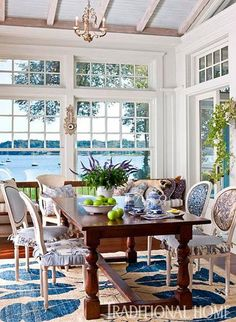 This glassed-in breakfast room features a palette of rich blues to complement the sweeping water views - Traditional Home® / Photo: Bruce Buck / Design: Eliza Gatfield