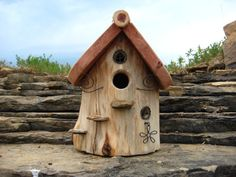 A very unique birdhouse made from cedar log. The construction process for this birdhouse involves cutting logs to length, stripping bark to reveal the natural beauty of the grains in the log, hollowing out the log, then adding a variety of wire and stone accents. Pictured is a hanging birdhouse where the bottom can be easily removed for seasonal cleaning.