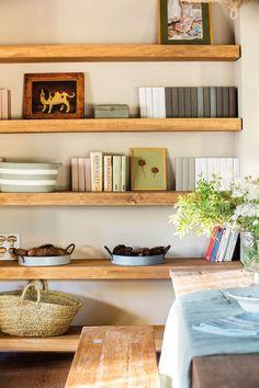 00443223. Libros, cuadros y pequeños objetos sobre las baldas de madera de la pared_00443223