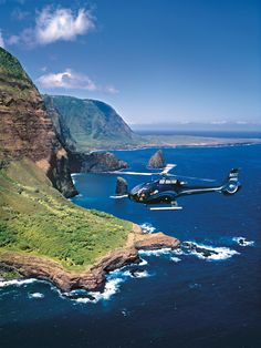 A Blue Hawaiian Eco-Star helicopter  exploring the Molokai coastline, Hawaii. Tour left from Maui.