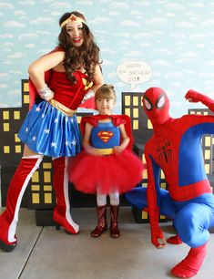 birthday girl in the photo booth with her superhero special guest entertainers, Wonder Woman and Spider-Man, who did magic, superhero training, flips, face painting and balloon animals.