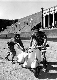 Charlton Heston e Stephen Boyd spingono una vespa sul set cinematografico.  1959