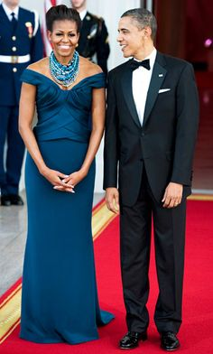 "Marchesa | Belle of the ball! The First Lady chose a teal Marchesa off-the-shoulder gown for the White House State Dinner in March 2012, which she accessorized with a necklace made from strands of teal, blue, silver and white pearls layered over a giant rhinestone piece. ""I love the addition of texture with the Tom Binns necklace,"" Roksanda Ilincic, who dressed Obama for the evening, said at the time of Obama, who added rhinestone earrings to complete her look."