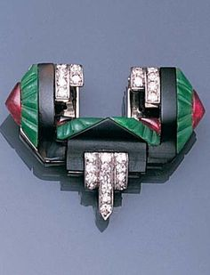 An Art Deco jade, onyx and ruby clip brooch, circa 1925. Of abstract geometric design, composed of carved jadeite and buff top ruby terminals, centring on an openwork rectangular onyx plaque, with cascading single-cut diamond highlights, width 3.1cm., fitted Tessiers ltd case. #ArtDeco #brooch