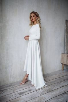 The Dalarna wedding dress from Mila Bridal is made from elegant crepe fabric and features a high-low skirt. The top and bottom can easily be made into separates. You're guaranteed a fuss-free celebration while wearing this clean number. #weddingdress #highlowdress #modestwedding #weddinggown #simpleweddingdress