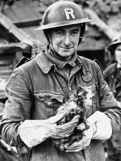 A rescue worker holds a disheveled cat taken from the ruins of a bombed London House, Feb. 14, 1941 following an air raid on the British capital. London Blitz WWII