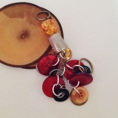 Amuleto realizzato con grandi bottoni vintage che giocano con i toni del rosso e dell'arancio.