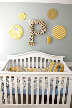 Complete DIY nursery tutorial - bedding, scrapbook paper mobile, giant rosette wall letter, fabric polka dots, pillows, and more. (This nursery in particular is yellow and gray)