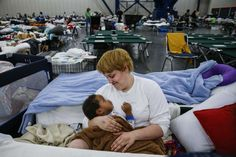 Shiann Barker holds her nephew, Brayln Matthews Sims Jr., 1, between cots at the George R. Brown Convention Center where nearly 10,000 people are taking shelter after Tropical Storm Harvey Wednesday, Aug. 30, 2017 in Houston. They have ben at the shelter since Sunday after they evacuated from the Clayton Homes neighborhood. Photo: Michael Ciaglo, Houston Chronicle / Michael Ciaglo