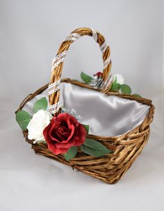 Rustic medium sized willow wicker Basket with beautiful white and red roses. Green leaves and silver flora accent the flowers. White ribbon adorns the handle with satin lining.  Lining comes it either white or silver or GOLD Flower Choice and ribbon colors adjusted upon request.  A Gold Lining makes this an excellent basket for Beauty and the Beast themed Weddings!  Basket size: 12in wide x 9in deep 5.5in basket height, 12in high with handle