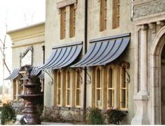 Standing seam copper awnings with wrought iron brackets...