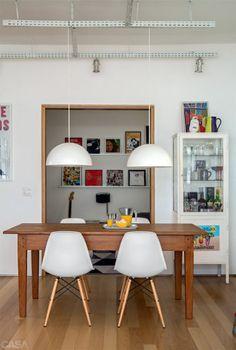 """Os pendentes sobre a mesa de jantar são da Ikea. Spots presos a trilhos aparentes iluminam os espaços. """"Assim, não é preciso rebaixar o teto"""", diz Isabella."""