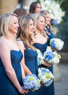 The bridesmaids are wearing beautiful blue Amsale gown and holding color matching bouquets.