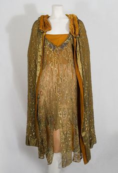 Gold metallic lace evening ensemble (dress and cape) with jewel-tone glass bead and faux pearl embellishment, c.1925. The dress also has a burnt orange silk chiffon slip, the top of which is lined with silk crepe, making the slip appear darker. The collar of the cape is ruched and padded. The cape is totally lined with matching burnt orange silk velvet.