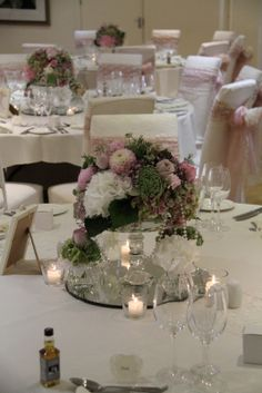 The low table design alternative our beautiful Crystal Cake Plinths againg swathed in pearls and surrounded by posies of fresh flowers and tea light votives