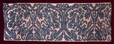"""Fragment of a border with a symmetrical scrolling vine pattern in green on gauze weave.    This fragment is medium: linen, silk technique: needlework on gauze weave.    This fragment is from Italy and dated """"17th century""""."""
