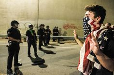 Los Angeles: With the American flag draped over his mouth, one protester put his hands up ...