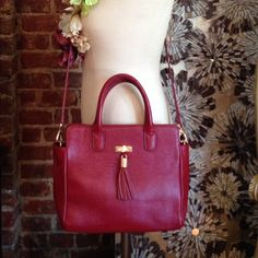 "Gorgeous leather Onna Ehrlich purse This dark red leather bag from Onna Ehrlich is absolutely stunning.  Can be worn as a cross-body or on the shoulder.  On trend tassel detail on the front.  Zipper closure with inside pocket.  Will also include the dust bag with purchase.  In beautiful condition - only used a few times.  Width: 12"" Height: 10"" Depth: 6"" Bags"