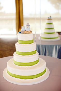 White four tiered cake with light green borders and a lovebirds in a nest topper - photo by San Francisco based wedding photographer Meg Perotti