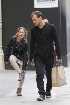 Jude Law Photos Photos - Jude Law has a busy afternoon as he takes his children Rudy and Iris street art shopping in Soho, New York City. Law had his hands full with shopping bags and was all smiles with his kids but the actor's mood turned sour when he saw photographers. At one point, Law stepped away from his children and can be seen having a strong word with a photographer. - Jude Law and Family Shopping in NYC