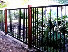 Black flat top aluminium fencing with timber posts by fencepac | http://www.fencepac.com.au/residential/fences/aluminum/