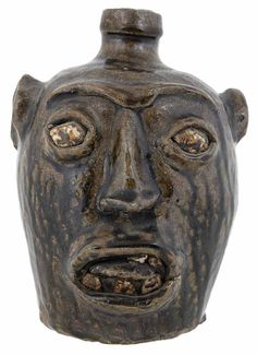 Rare Edgefield Stoneware Face Jug (Edgefield District, South Carolina, 1860s), dark to light olive runny alkaline glaze over entire body, 7 in. Examples of Edgefield Face Jugs with extended tongues are rare. One other known example is in the Collection of the Chipstone Foundation, (see Ceramics in America edited by Robert Hunter, 2013, pg 27 figure 28.). Private Collection, Atlanta, Georgia. Brunk, 01/28/2017, $44,000 + prem.