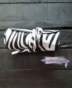 Black and white zebra cosmetic bag! The outer part is for all of your make-up brushes and tubes. It can be rolled up and tied on it's own or around the little bag. There are 9 slots for your brushes and tubes. Buy it now for just $10 at Jourdan's Jewels.