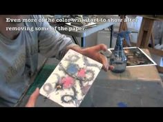 Randy L. Purcell demonstrates how he uses magazine pieces to transfer ink on to wax.