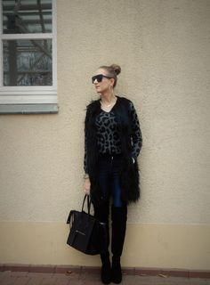 SHADES OF K by Karen   wearing skinny blue jeans, long fur vest, animal print knit sweater, black over-the-knee boots, black bag, black oversized sunglasses, hoop earrings, winter outfit, winter style, winter street style
