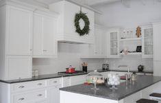 White Farmhouse Kitchen decorated for Christmas! Boxwood Wreath on the hood.