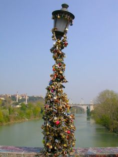 The famous padlock-covered lamppost of The Milvian Bridge in Rome, Italy. Since 2006, lovers have attached initialled locks to the post and then thrown the keys into the Tiber river as a sign of their love.
