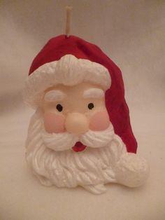Vela no formato do rosto do Papai Noel, produzida em cera a base de óleo vegeta, pintada à mão com tinta a base de água.
