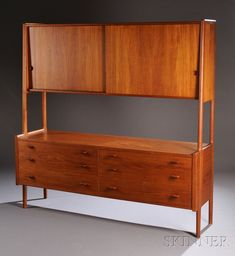Hans Wegner for Ry Mobler High Cabinet, Teak and birch, Denmark, 1962, Over head compartment with two sliding panel doors opening to a total of five adjustable shelves over a credenza containing six drawers with shaped teak pulls, 71 H. x 71 L. x 19.5 D.