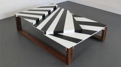 Shown in reclaimed teak, powder coated aluminum, vinyl cut, 60×42.25×16.25H, 2011 DESCRIPTION The War Craft Coffee Table wears an interpretation of Dazzle camouflage that was used on battleships to confuse enemy ships. Through high contrast and disrupted lines, Uhuru graphically breaks up the pattern for a functional coffee table.  The levels represent the decks of the battleship, …