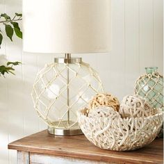 At home in a farmhouse loft or cozy coastal retreat, this distinctive table lamp showcases a glass base accented by rope netting.